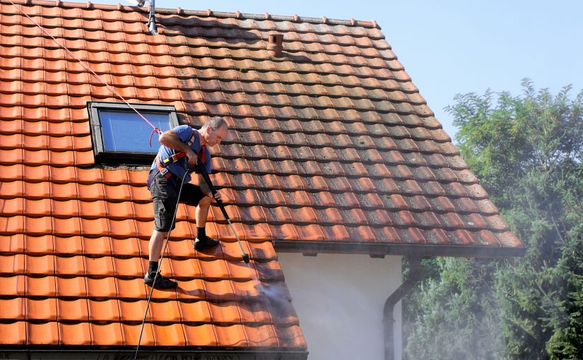 man pressure cleaning roof