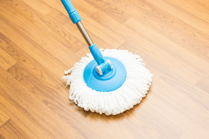 Mopping wooden floor with blue mop