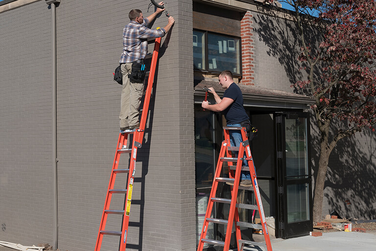 Two men working on the extension ladder