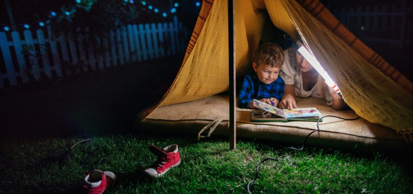 Boy camping with his dad in the backyard