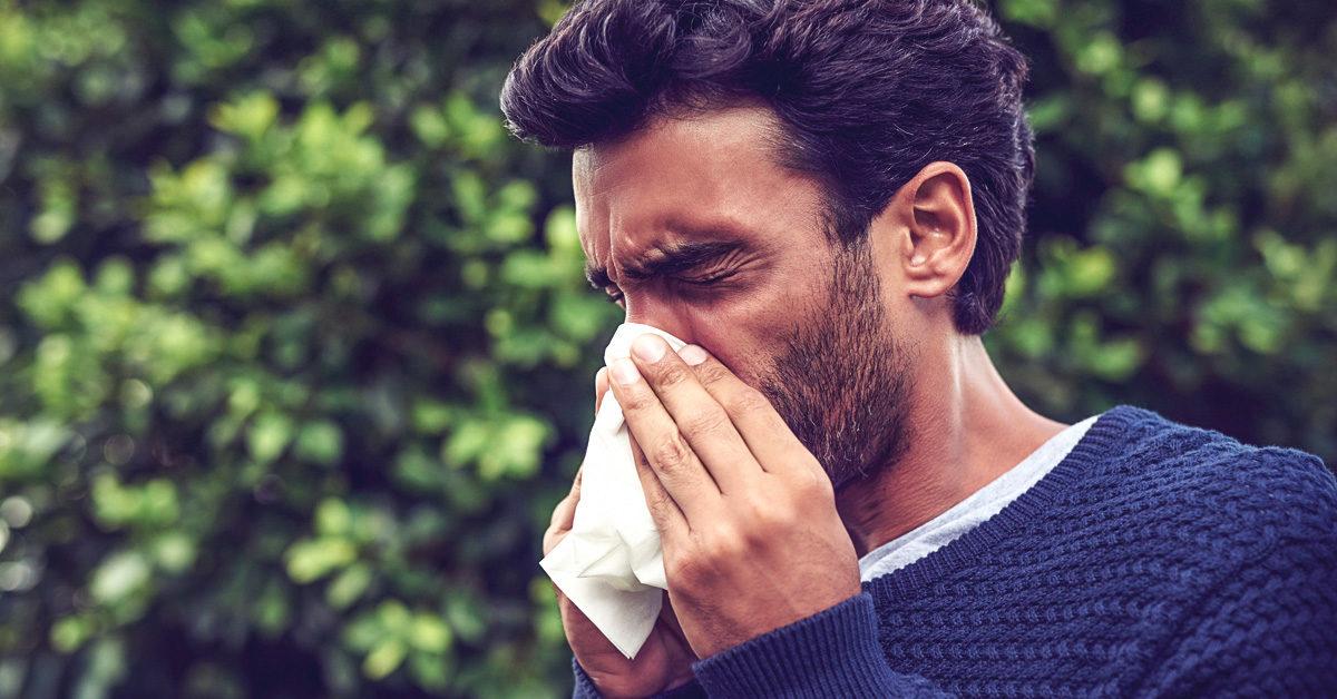 Man sneezing outdoors