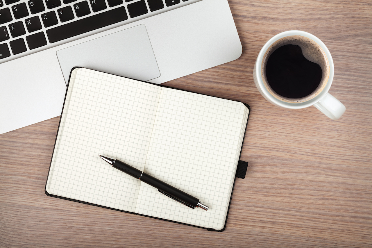 Coffee notebook and laptop on desk