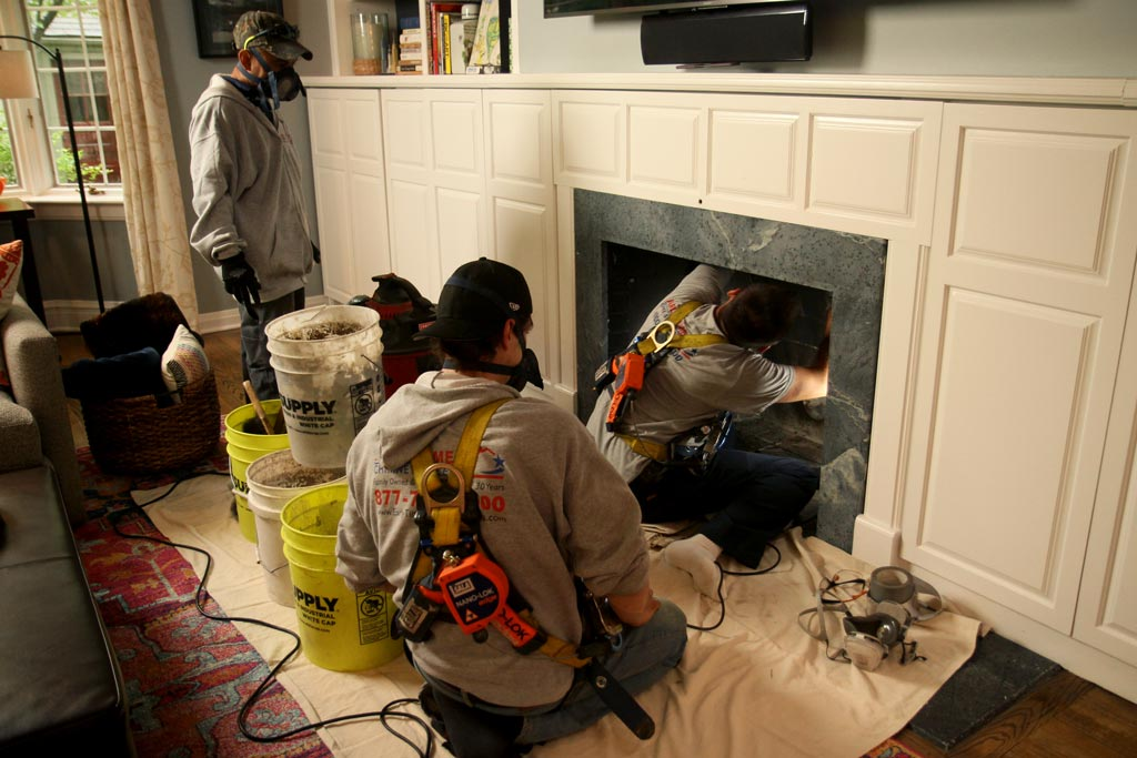three people cleaning fireplace