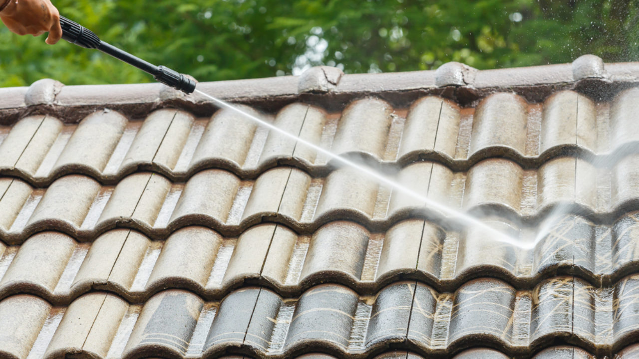 man cleaning roof with pressure cleaner