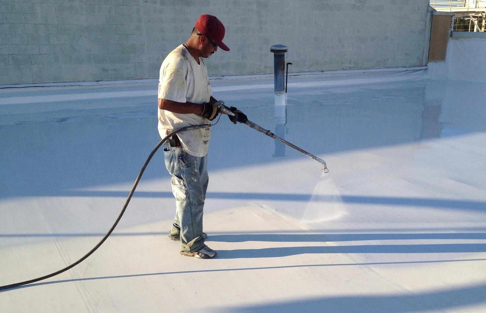 White t shirt man spraying roofing