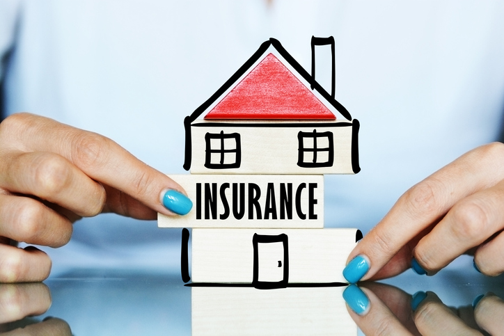 Home insurance in hand with blue nail paint